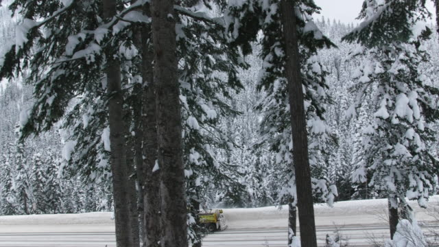 Jib Crane Shot of Snowplow on Snow Covered Mountain Road with Cars video