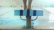 Jib Shot from Back Side of Professional Female Swimmer Preparing and Jumping Off the Starting Block into Pool. video