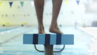 Jib Shot from Back Side of Professional Male Swimmer Preparing and Jumping Off the Starting Block into Pool. video