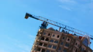 Jobs construction crane over multi-storey residential house and sky. video