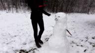 Jocose woman finish snowman, put carrot lower than needed video