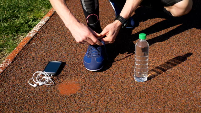 Jogger with smartwatch tying shoelaces and picking up smartphone with earphones and water bottle video