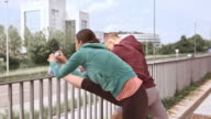 LD Jogging couple stretching their legs on a fence video