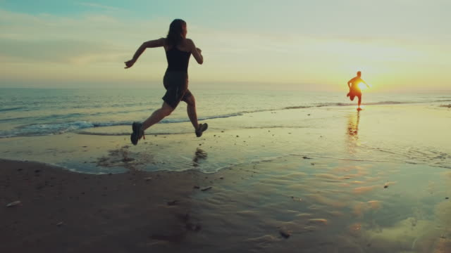 Jogging on the beach: running at sunset SLO MO video