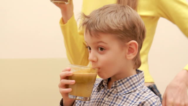 joyful boy drinking fresh juice with aunt in kitchen video