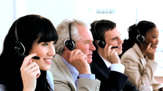 Joyful call centre agents sitting while wearing headsets video