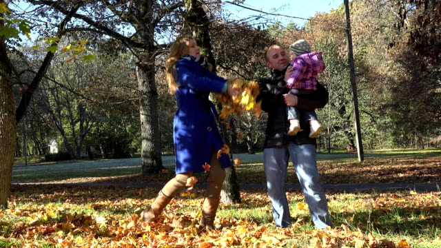 joyful couple with baby throw autumnal leaves in beautiful park. FullHD video