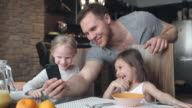 Joyful father and daughters making faces for selfies video