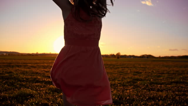SLO MO Joyful girl in the meadow at sunset video