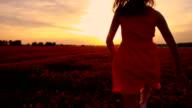 SLO MO Joyful girl running among flowers at sunset video