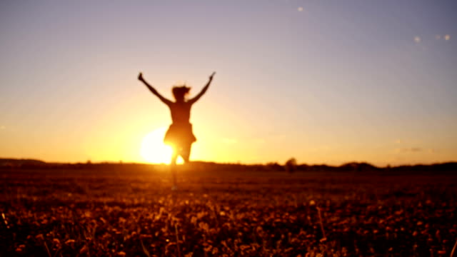 SLO MO Joyful girl running in grass at sunset video