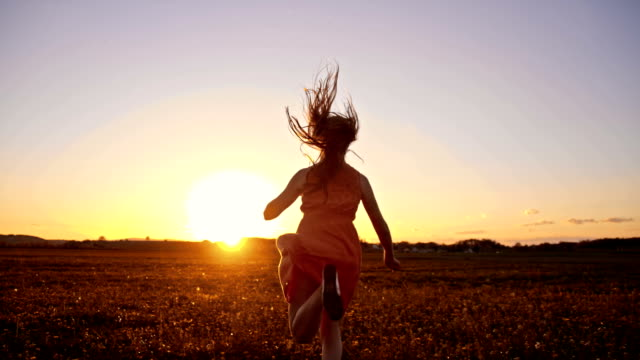 SLO MO Joyful girl running in grass at sunset video