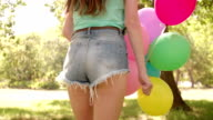 Joyful girl with colourful balloons in a sunny park video