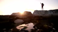 Joyful hipster teen dancing on rocks with arms out excitedly video