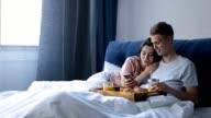 Joyful lovers having breakfast in bed at home video