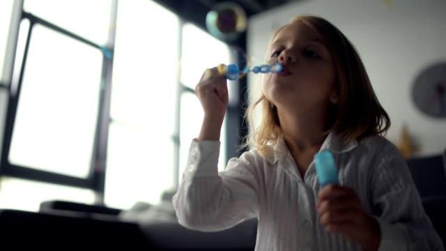 Joyful pretty girl blowing soap bubbles video