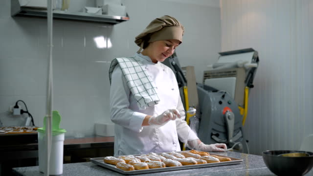 Joyful woman standing behind a small pastry toque table on which lay a tray of eclairs and carefully sprinkles of sugar video