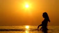 SLOW MOTION: Joyful woman standing in shallow ocean and splashing water around video