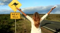 Joyful woman stands arms outstretched near kangaroo crossing sign video