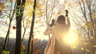 SLO MO Joyful woman throwing autumn leaves over herself video