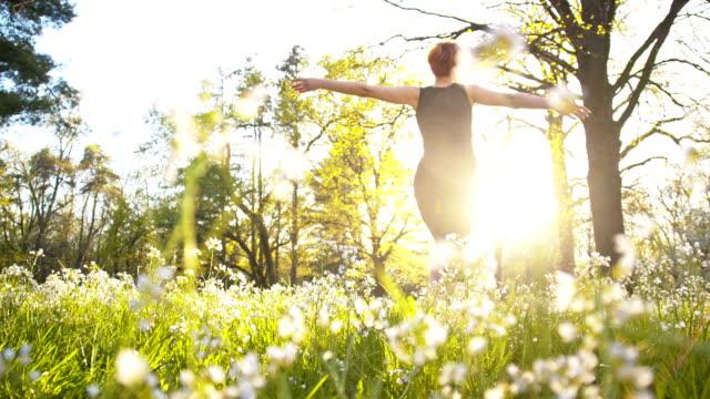 SLO MO Joyful woman twirling in spring meadow video