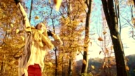 SLO MO Joyful woman twirling under falling autumn leaves video