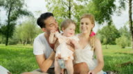 CLOSE UP: Joyful young father tossing his smiling baby girl up and down video