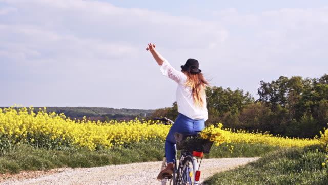 SLO MO Joyful young woman cycling along colorful canola fields video