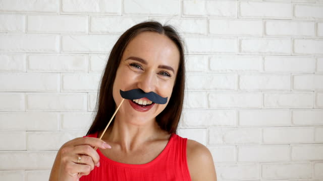Joyful young†woman holding funny moustache on stick making funny faces video