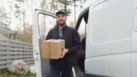 Joyfull Delivery Man Comes Out of His Cargo Van and Goes Towards Camera. video