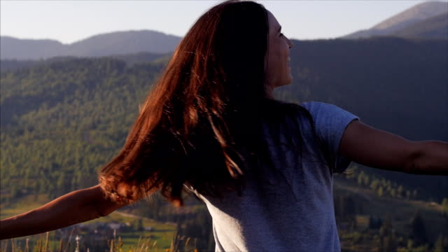 Joyous woman whirling at sunset in mountains video