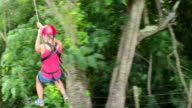 Joyous young girl smiling and having fun while zipling above lush rainforest video
