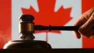 Judge calling order with hammer and gavel in canadian court with flag background video
