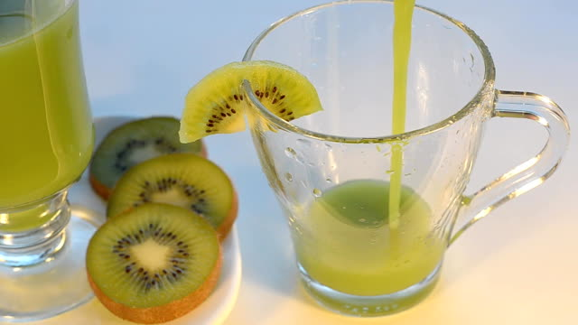 KIWI juice poured into a Cup and add pieces of fruit. Selective focus, artificial light. video