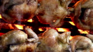 Juicy whole roasted chickens on flames video