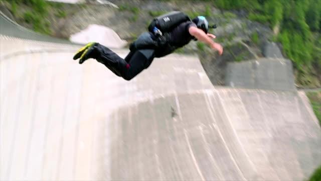 BASE jumper plunges down concrete dam face video