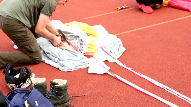 BASE jumper prepares parachute for jump, parking area video