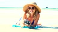 junge frau im blauen bikini liegt am strand mit einer vintage kamera und hat einen sonnenhut auf video