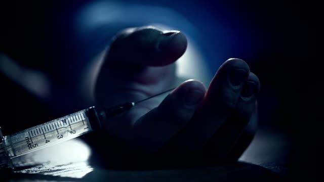 Junkie hand Fall to floor pricked heroin or meth drugs, drops the syringe video