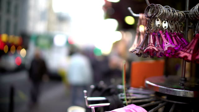 Keychains and souvenirs hanging on stand, tourism and shopping in Paris video