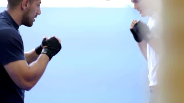 Kickboxer is practicing kick in a boxing gym video