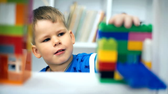 Kid boy playing toy blocks on floor at home video