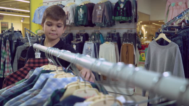 Kid choose garment in the shop video