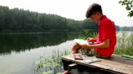 Kid drawing a summer landscape with forest lake sitting on a jetty video
