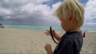 A kid finds a twig on the beach video