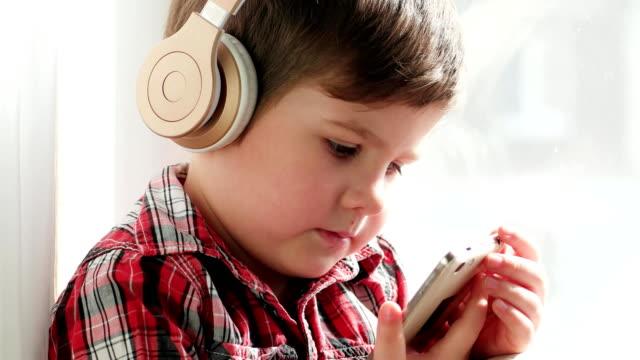 kid in headphones listening to music, boy wearing checkered shirt watch cartoons on smartphone video
