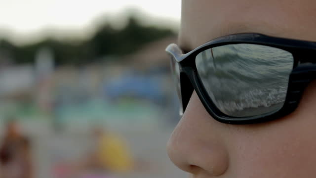 kid in sunglasses looks at the sea video