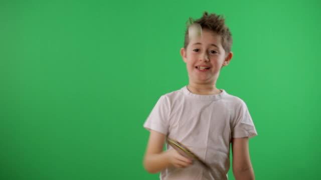 Kid juggles the ping pong ball. Green screen video