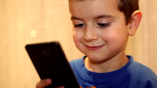 Kid look in mobile phone video