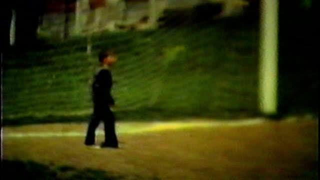 Kid playing soccer kicking football. Old vintage video video
